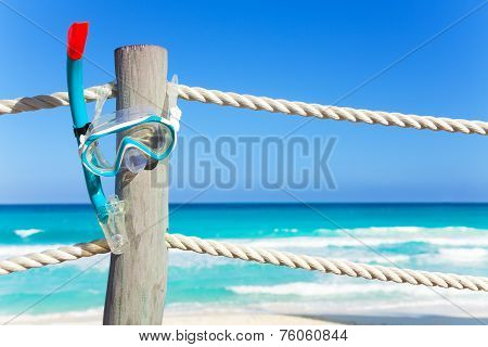 Blue snorkeling mask hangs on the wooden pier