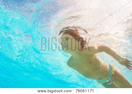 Smiling boy swimming under crystal-clear water