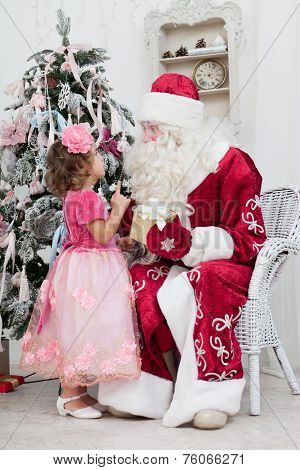 Little girl talks to Santa Claus near a Christmas fir-tree