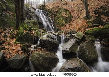Waterfall on mountain river in forest withcliffs