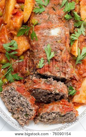 Homemade meatloaf baked in tomato sauce with peas and potatoes seen from above