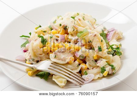 Tuna salad with pasta, onion, sweetcorn, parsley and mayonnaise on a plate with a fork