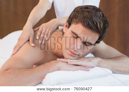 Close up of a handsome young man receiving shoulder massage at spa center