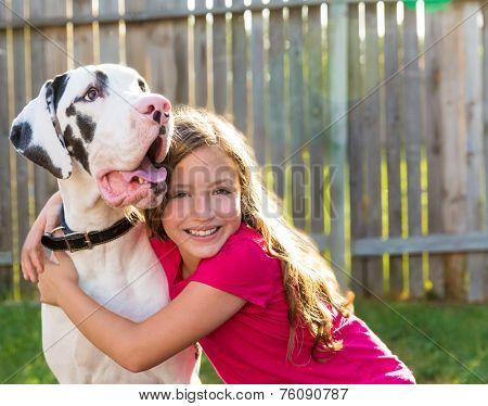 great dane and kid girl hug playing together at backyard outdoor