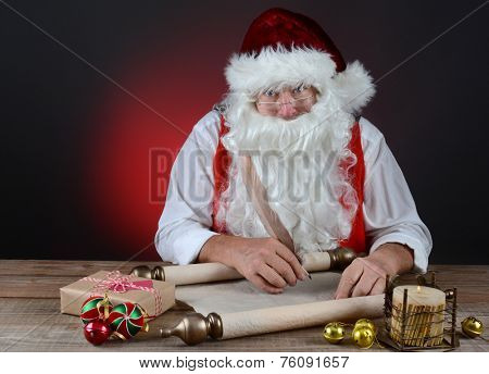 Santa Claus checking his naughty and nice list on a scroll of parchment paper. Santa is seated at a rustic wood table. Horizontal format on light to dark red background.