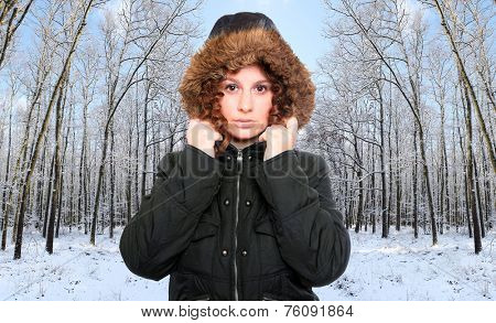 Young woman dressed in warm jacket with fur hood for frosty weather.