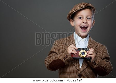 Cute boy with vintage photo camera on the grey background. ( Retro style.)