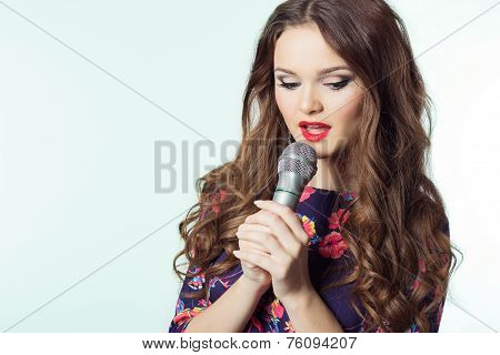 portrait of a beautiful elegant girl singer brunette with long hair with a microphone in his hand
