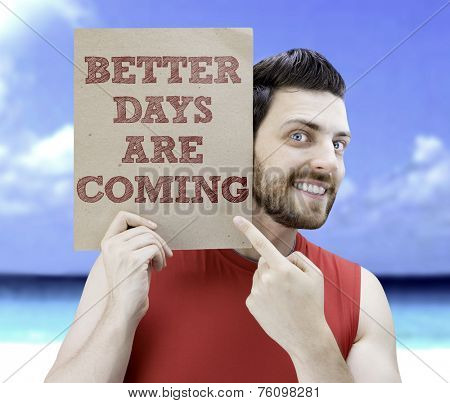Man holding a card with the text Better Days Are Coming on a beach background