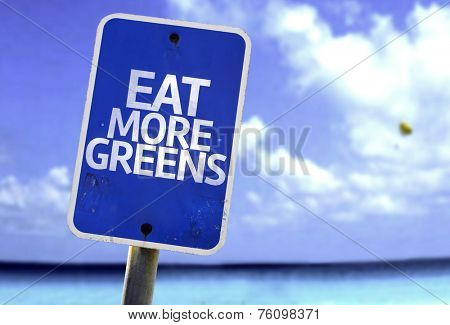 Eat More Greens sign with a beach on background