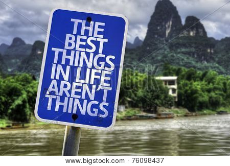 The Best Things In The Life Aren't Things sign with a forest background