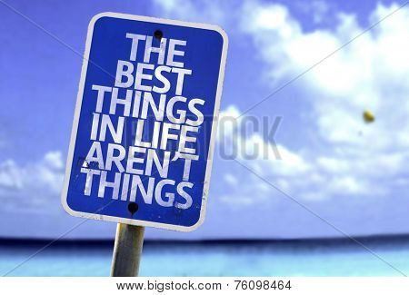 The Best Things In The Life Aren't Things sign with a beach on background