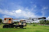 stock photo of boom-truck  - Old automobile crane with telescopic boom outdoors over blue sky - JPG