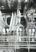 stock photo of dishwasher  - Open dishwasher with clean utensils in it - JPG