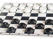 image of draught-board  - Black and white draughts on a board close up on awhite background - JPG