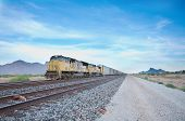 stock photo of chug  - Cargo locomotive railroad engine crossing Arizona desert wilderness during early evening - JPG