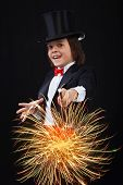stock photo of magic-wand  - Young magician boy using his magic wand to conjure up sparks and fireworks - JPG