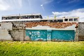 stock photo of old stone fence  - Abandoned factory behind old brick fence on a sunny day - JPG