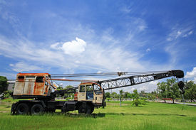 foto of boom-truck  - Old automobile crane with telescopic boom outdoors over blue sky - JPG