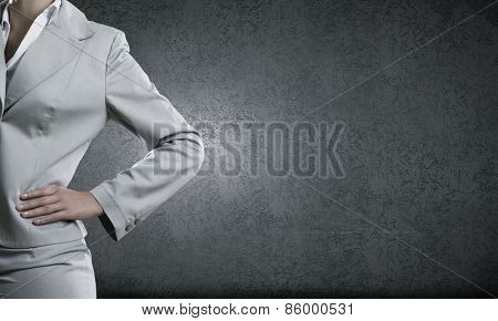 Chest view of businesswoman in suit against cement wall