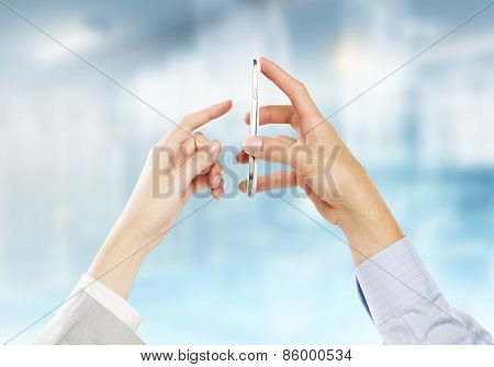 Two business people using one mobile phone at the same time