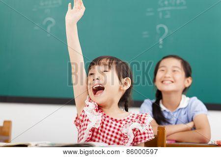 Happy School Children  Raised Hands In Class
