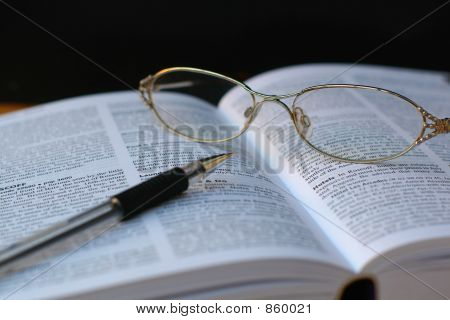 pen and glasses on book page