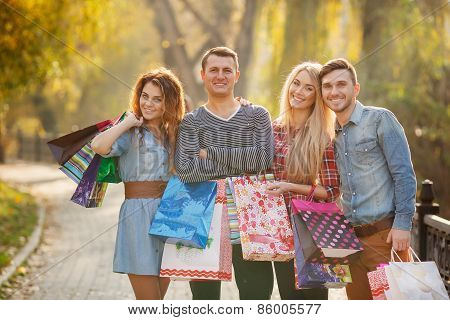 Two young couples in the Park with bags on the way to the Mall.