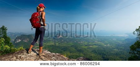 Lady hiker with backpack standing on top of the mountain and enjoying valley view