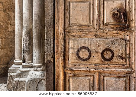 Ancient wooden door and marble pillars at the entrance to Church of the Holy Sepulchre in Jerusalem, Israel.
