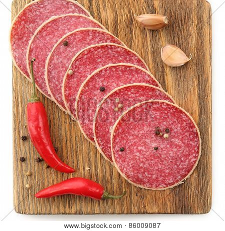 Slices of salami with chili pepper and spices on wooden cutting board isolated on white