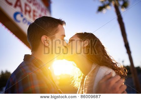 romantic couple kissing by welcome to las vegas sign with golden lens flare