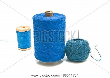 Ball Of Yarn And Spools Of Thread On White