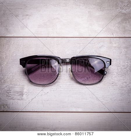 black sunglasses on wood floor