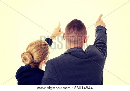 Successful business couple pointing away.