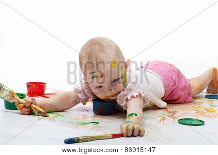 Little Girl Soiled By Bright Paints Lies And Tries To Keep Step With A Brush