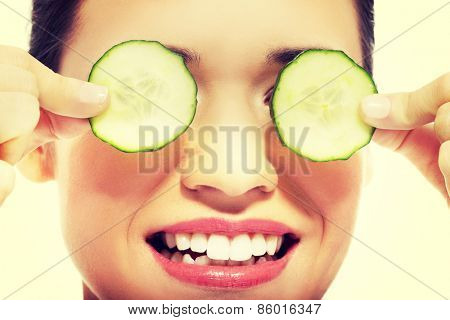 Beautiful young woman receiving facial mask of cucumber.