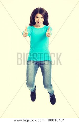 Casual woman jumping showing OK. Isolated on white.