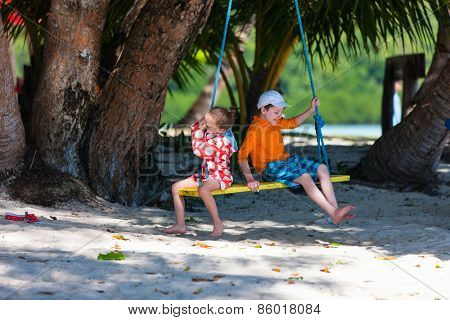 Kids having fun on swing on summer day