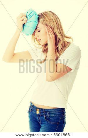 Beautiful woman with ice bag, having headache.