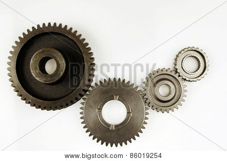 Four metal gears on plain background