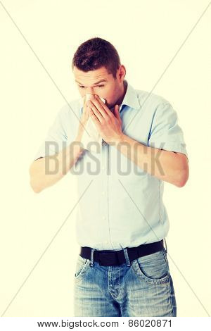 Sick young man blowing her nose
