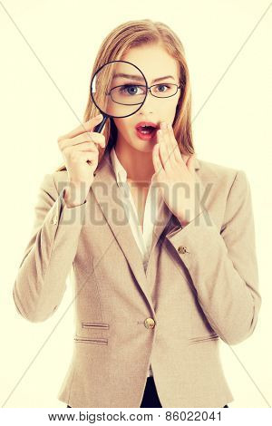 Young smiling business woman looking into a magnifying glass.