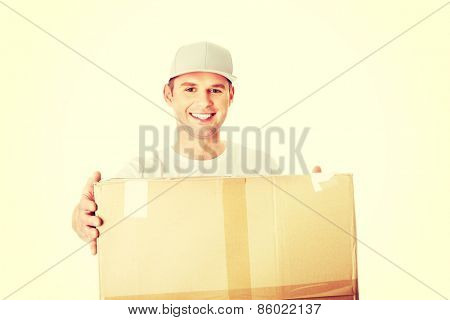 Young attractive courier guy delivering brown boxed parcel