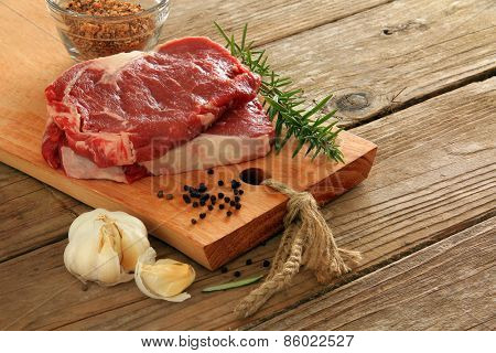 Raw prime rib beef steaks with spices, garlic and rosemary. Also available in vertical.