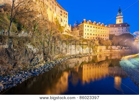 Castle with the famous round tower in Cesky Krumlov, Czech Republic is reflecting in the river Vltava in the evening