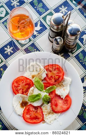 A cheese platter with tomatoes and basil