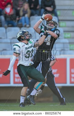 INNSBRUCK, AUSTRIA - MARCH 29, 2014: CB Christian Kober (#31 Dragons) and WR Clemens Erlsbacher (#84 Raiders) fight for the ball in an AFL football game.