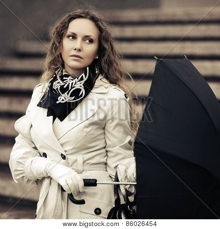 Beautiful fashion woman with umbrella on a city street