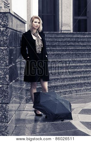 Young blond fashion woman with umbrella at the wall